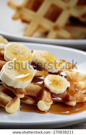 Waffles with bananas covered with maple syrup - stock photo