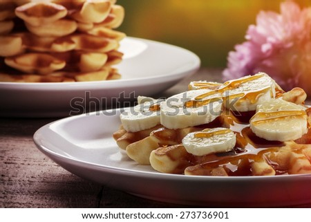 Waffles with bananas covered with maple syrup, processed with vintage filter - stock photo
