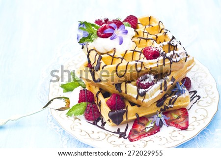 Waffles with cream, berries and chocolate sauce - stock photo
