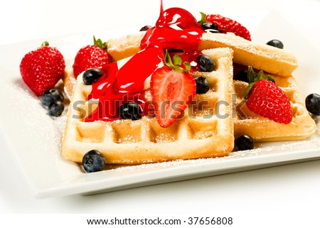 Waffles with fruit and red strawberry syrup