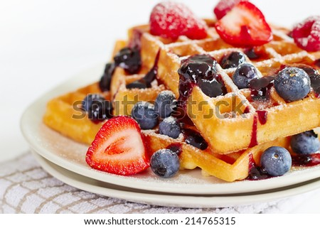 Waffles with honey, jam, and berries on a white plate, in close up view - stock photo
