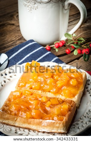 Waffles with peach jam on white plate.. - stock photo