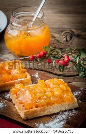 Waffles with peach jam on wooden board. - stock photo