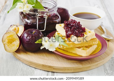 waffles with plum jam, ripe plums and tea on a cutting board.selective focus - stock photo