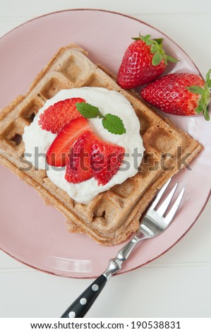 Waffles with strawberries for breakfast - stock photo