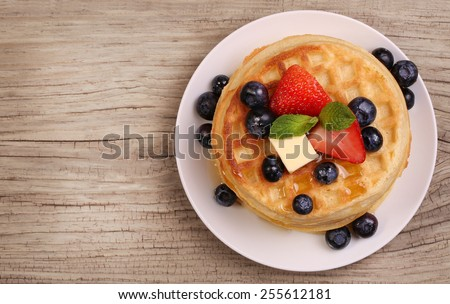 Waffles with Strawberry and Blueberry over wooden background - stock photo