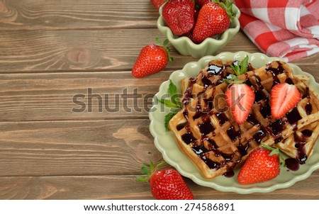 Waffles with topping and strawberries on a brown background
