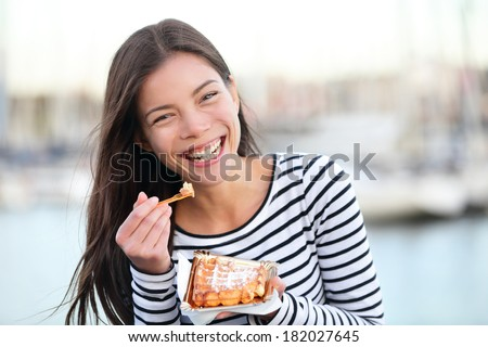 Waffles - woman eating waffle happy outdoors smiling laughing looking at camera. Beautiful girl eating food snack outside. - stock photo