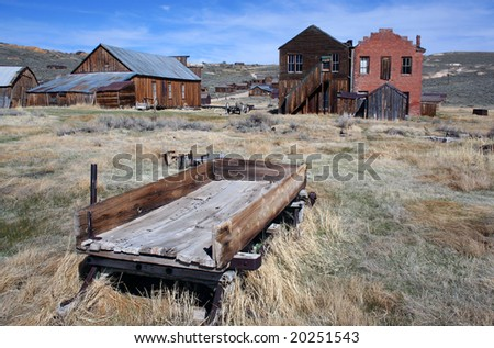 Wagon and old historical buildings from the wild west town of Bodie, California - stock photo