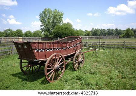 Wagon sits on farmstead. - stock photo