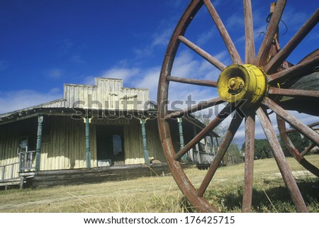 Wagon wheel and old building in South TX ghost town - stock photo