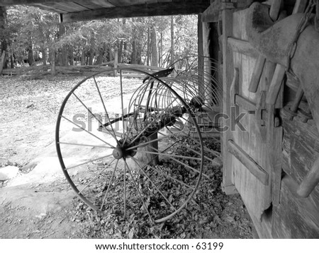 Wagon wheel at old barn - stock photo