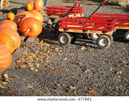Wagons and pumpkins on a fall day at a New England farmstand - stock photo