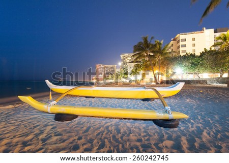 Waikiki beach at night with a yellow outrigger canoe - stock photo