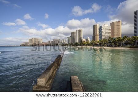 Waikiki beach breakwater in early morning light. - stock photo