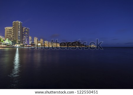 Waikiki Beach Honolulu Hawaii resort hotels and diamond head peak at night. - stock photo