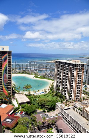 Waikiki beach is known as the world's greatest beach. Surfers ride the waves as vacationers play in the sand.