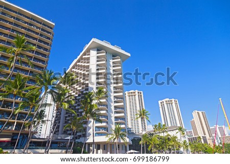 Waikiki beach waterfront buildings under tropical blue sky, Hawaii, USA. Modern buildings on a street with tall palm trees.