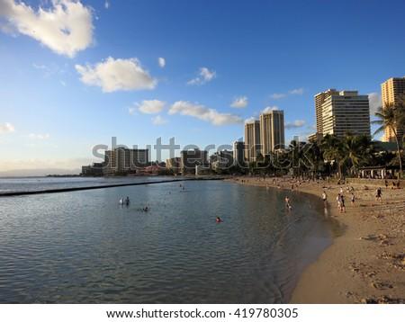 WAIKIKI - FEBRUARY 7: People play in water and beach in Waikiki at dusk on  February 7, 2016. - stock photo