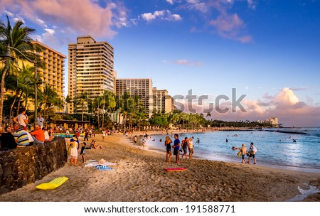 WAIKIKI, HI - APRIL 27 - Tourists on the beach front at sunset on Waikiki beach April 27, 2014 in Oahu. Waikiki beach is beachfront neighborhood of Honolulu, best known for white sand and surfing. - stock photo