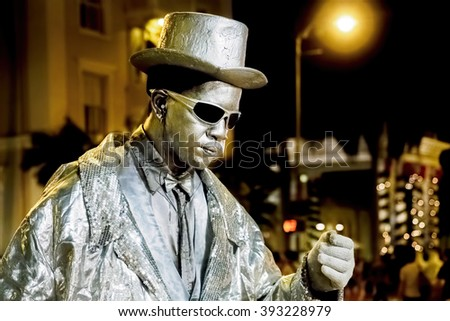 Waikiki, Honolulu, Hawaii, USA - Dec 12, 2015: Night street performer keeping still. His face is painted glittery silver to match his clothing color. People watch in awe and often donate some money.