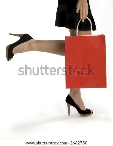 waist-down view of woman carrying shopping bag - stock photo