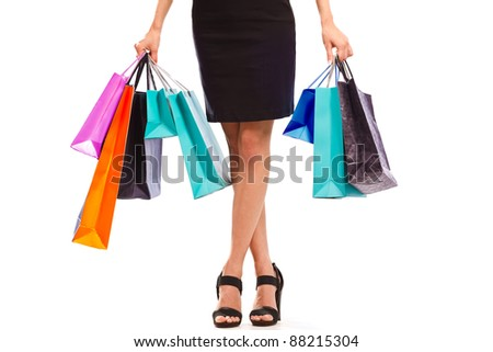 Waist-down view of young woman carrying colorfull shopping bags - stock photo