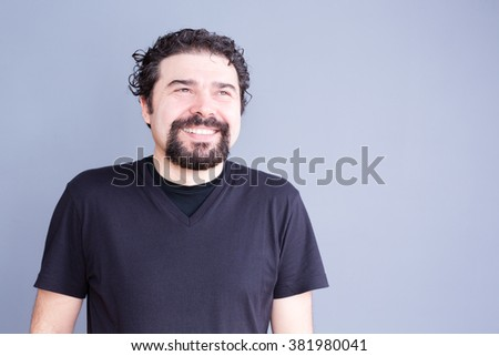 Waist Up Casual Portrait of Man with Beard and Curly Hair Wearing Dark T-Shirt Smiling and Laughing Joyfully in Studio with Copy Space