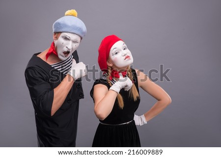 Waist-up horizontal portrait of couple of two mimes looking at the camera and showing that they are dangerous threating isolated on grey background with copy place - stock photo
