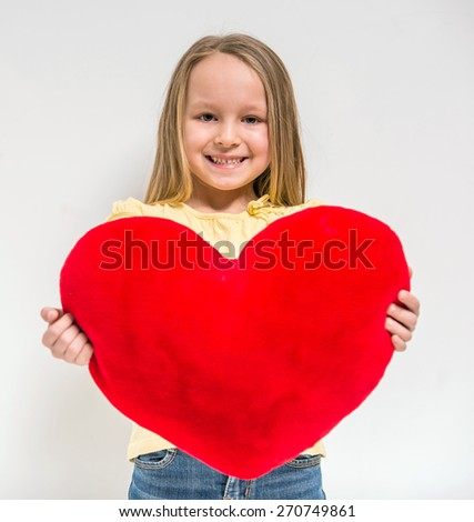 Waist up. Love. Cute little girl holding big red heart on grey background. - stock photo