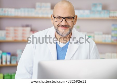 Waist Up Occupation Portrait of Friendly Mature Male Pharmacist Wearing White Lab Coat and Working on Computer Behind Counter in Drug Store Pharmacy - stock photo