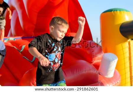 Waist up of blond boy (7-9 years) wearing black t-shirt with colorful print playing in red bouncy castle - stock photo