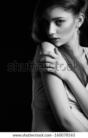Waist up of pretty woman with beauty long hair, natural make-up and hugging herself, looking at camera. Black and White photo - stock photo