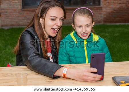 Waist Up of Woman and Girl Taking Selfie Portrait with Modern Cell Phone or Looking at Something Funny on Screen While Sitting at Picnic Table Outdoors - stock photo