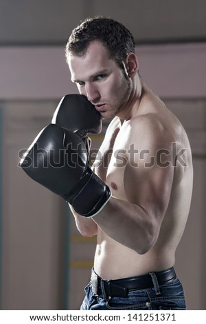 Waist-up of young male boxer in gym - stock photo