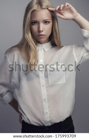 Waist up of young sexy female with long blonde hair and natural make-up, with hand near her hair, dressed in white blouse and looking at camera - stock photo