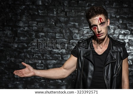 Waist up photo of a young man with bloody make up looking tired, standing with his hand stretched aside to copy space on the black brick wall