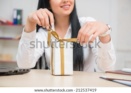 Waist up portrait business woman sitting at the desk  with computer opening a white present box with gold ribbons in the office interior with selective focus on a gift box - stock photo