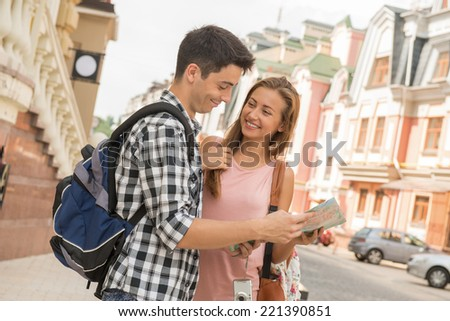 Waist-up portrait of a beautiful couple of tourists holding a map in their hands and smiling looking on each other while deciding where to go, concept of summer holidays and tourism - stock photo