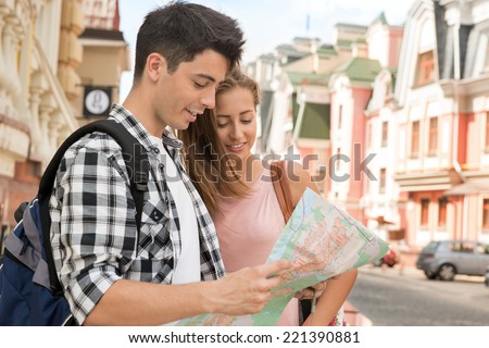 Waist-up portrait of a beautiful couple of tourists holding a map in their hands and smiling hugging each other while deciding where to go, concept of summer holidays and tourism