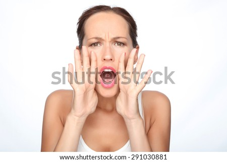 Waist up portrait of a beautiful woman with brown hair standing and shouting holding her hands near her mouth to be louder, isolated on white background