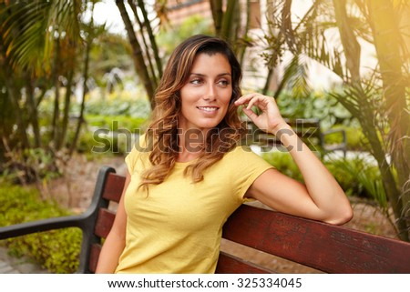 Waist up portrait of a cheerful lady in yellow shirt looking away while sitting on bench - stock photo