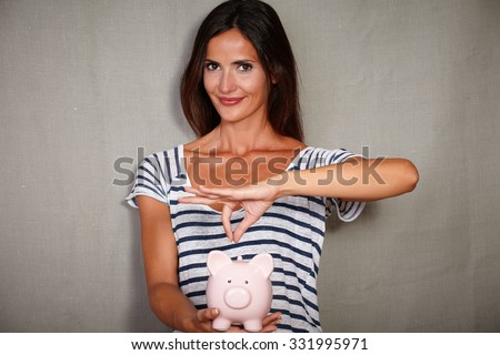 Waist up portrait of a happy woman in her 30s holding a piggy bank with savings