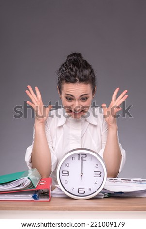 Waist-up portrait of angry girl sitting at the table in office with a pile of documents and a big clock and breeding her hands because she has no time, isolated on grey background with copy place - stock photo