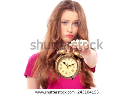 Waist-up portrait of beautiful frustrated girl holding an alarm clock in her hand and looking at the camera, with selective focus on a clock isolated on white background  - stock photo