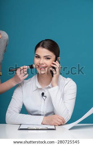 Waist up portrait of beautiful woman reporter with Caucasian appearance, who is smiling and looking at the camera speaking the mobile phone while sitting at the desk. - stock photo