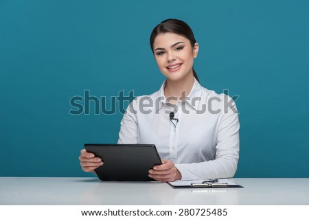 Waist up portrait of elegant woman reporter with Caucasian appearance, who is telling news and smiling and looking at the camera, sitting at the table and holding the notebook in her arms. - stock photo