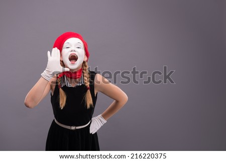 Waist-up portrait of funny female mime in red head and with white face very loudly shouting and looking at the camera isolated on grey background with copy place - stock photo