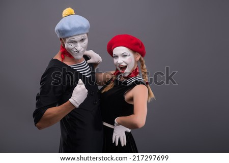 Waist-up portrait of funny hugging mime couple saucy looking at the camera, male mime showing on himself isolated on grey background with copy place - stock photo