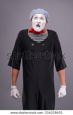 Waist-up portrait of funny male mime with grey hat and white face disappointed looking up and holding his hands omitted down isolated on grey background with copy place - stock photo
